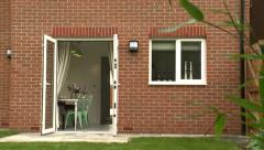 Pan down past Plant of Back Garden House Stock Footage