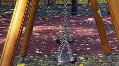 Two empty swings moving on the playground, autumn leaves, fall season Stock Footage