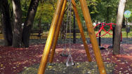 Stock Video Footage of Two empty swings moving on the playground, autumn leaves, fall season