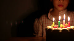 Asian girl blowing birthday cake candles. - stock footage