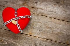 heart with chains on wooden background - stock photo