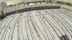 Many railroad tracks covered by snow near gates of train depot - stock footage