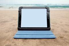 Tablet device on beach - stock photo