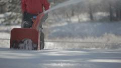 Worker pushing snow thrower after winter blizzard snowfall in residential area Stock Footage