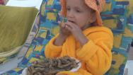 Stock Video Footage of Little Girl Eating Fried Fish with Lemon, Child, Kid on Beach Chair on Seashore