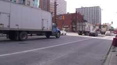 Stock Video Footage of 18 wheelers driving through a down town main street. #03B-26