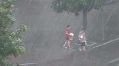 Women go across a road during a strong pouring rain Stock Footage