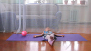 Stock Video Footage of a little girl plays the fool, doing exercises, yoga, play with a ball