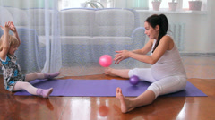 A little girl and a pregnant woman, play with a ball, do exercises, yoga Stock Footage