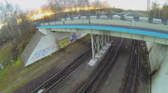 Railway tracks under bridge for cars at autumn evening Stock Footage
