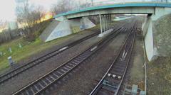 Railway tracks under bridge with car traffic at autumn evening Stock Footage