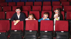 Family watching 3D movie and eating popcorn Stock Footage