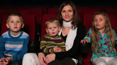 Woman with her two sons and daughter are sitting in the cinema Stock Footage