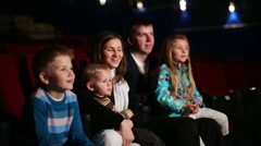 Young man and woman with three children watching family comedy - stock footage