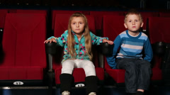 Little boy and girl with an interest watching a comedy at cinema - stock footage