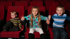 Three small children together watching a movie at the cinema Stock Footage
