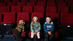 Three children in 3D glasses sit and watching a movie Stock Footage