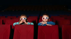 Boy and girl in 3D glasses sitting and watching a movie Stock Footage