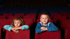 Little boy and girl watching a scary movie and hides - stock footage