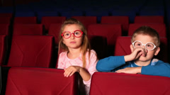 Little girl and boy watching a movie at the cinema Stock Footage