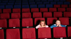 Boy and girl sitting alone in the cinema and watching a movie Stock Footage