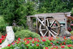 Flower garden and waterwheel Stock Photos