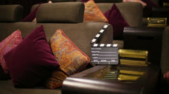 Movie clapper board on lounge with cushions in cinema theatre Stock Footage