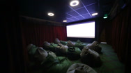 Stock Video Footage of Film trailer in children movie hall with soft ottomans in cinema