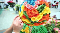 Woman makes ball shaped bright bouquet of roses at flower show Stock Footage