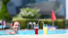 girl and woman swimming in the pool and drink beverage - stock footage