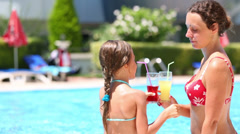 girl and woman drink beverage on the background of the pool - stock footage