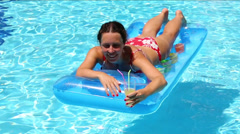Woman swims in pool on an air mattress and drinking a cocktail Stock Footage