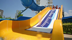 Two girls and a boy ride on the yellow water slide in the hotel Stock Footage