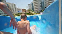 boy and two girls slips at a rate on the water slide - stock footage