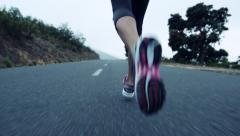 Woman running on road close up shoes steadicam shot Stock Footage