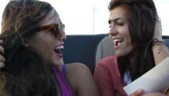Teen Girl Holds Photograph And Talks To Friend In The Backseat Of Convertible Stock Footage