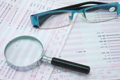 magnifier and spectacles on bank account - stock photo