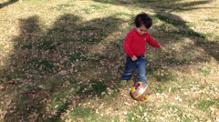 Funny boy playing with ball on grass with leaves Stock Footage