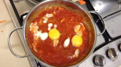 Shakshuka also known as eggs poached in a sauce of tomatoes Stock Footage