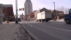 Stock Video Footage of 18 wheelers driving through a down town main street. #14-26