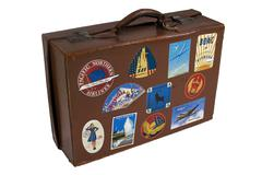 Vintage Suitcase with Travel Stickers - stock photo