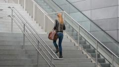 Woman walking up the stairs Stock Footage