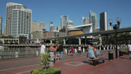 Stock Video Footage of tourists walking along promenade with views of cockle bay, darling harbour
