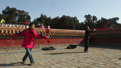 The old man and woman play diabolo together at temple fair Stock Footage
