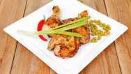 Stock Video Footage of meat food : chicken legs garnished with green peas and hot chili peppers plates
