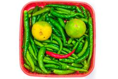 Green chilli peppers and lemon in box isolated on white background Stock Photos