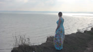 Stock Video Footage of Young girl in a beautiful dress is standing on the coast.