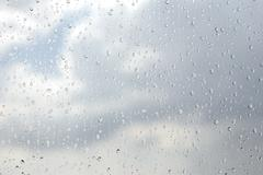 Raindrops flowing down on window glass abstract Stock Photos