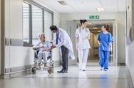 Stock Photo of senior female patient in wheelchair & doctor in hospital