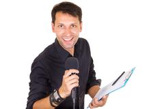 Handsome male journalist reporting news on microphone with notes Stock Photos